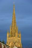 Kyrklig tornspira mot en stormig himmel Arkivfoto