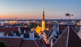 Kyrklig tornspira som tänds upp bland takblast arkivfoton