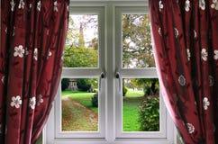 kyrklig trädgård till fönstret Arkivbild