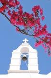 Kyrkliga Klocka och rosa färgblommor i Mykonos, Grekland Arkivbild