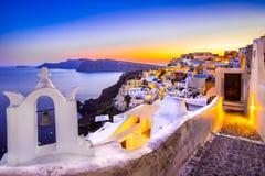 Kyrkliga klockor en solnedgång, Oia, Santorini, Grekland Arkivfoton