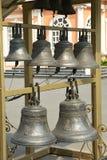 Kyrkliga klockor som i rad hänger Arkivbilder