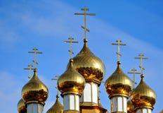 Kyrkliga kupoler med kors på en bakgrund av blå himmel Royaltyfri Bild