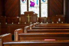 Kyrkliga kyrkbänkar med målat glass utöver predikstolen Arkivfoton
