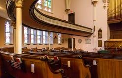 Kyrkliga kyrkbänkar under krökt balkong Arkivfoton