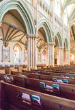Kyrkliga kyrkbänkar under vita bågar Arkivfoton