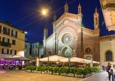 Kyrkliga Santa Maria del Carmine och fyrkant med restaurangen på natten i Milan Arkivfoton