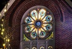 Kyrkligt fönster för målat glass på natten arkivfoto