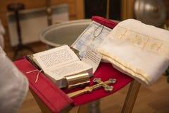 Kyrkligt redskap på ett altare, ollon, kors på det kyrkliga altaret, bibeln på tabellen, ceremoni av vattendopet Arkivbild