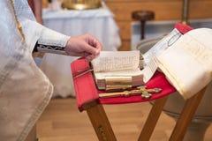 Kyrkligt redskap på ett altare, ollon, kors på det kyrkliga altaret, bibeln på tabellen, ceremoni av vattendopet Royaltyfri Foto