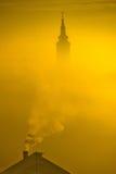 Kyrkligt torn för guld- soluppgång i dimma Royaltyfria Bilder