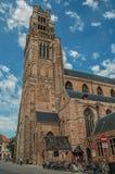 Kyrkligt torn, folk och cyklar på en gata av Bruges Fotografering för Bildbyråer