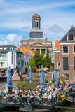Kyrkligt torn och kafé på Rhenkanalen, Leiden, Nederländerna Royaltyfri Bild