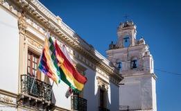 Kyrkligt torn och Wiphala och Bolivia flaggor - Sucre, Bolivia Arkivfoto