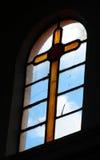 Kyrkligt vitral gult kors i ett fönster Arkivfoto