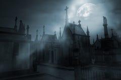 Kyrkogård i en dimmig fullmånenatt Arkivfoto