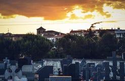 Kyrkogård med byn och soluppgångbakgrund arkivfoto