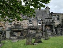Kyrkogård och byggnader i samma trädgård Arkivbild