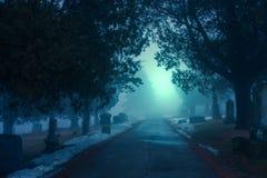 Kyrkogård på en dimmig afton royaltyfria foton