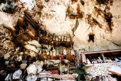 Kyrkogården med kistor som förläggas i grotta och balkonger med trästatytau-tau Gammal jordfästningplats i Londa, Tanaja, Indones Arkivbilder
