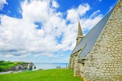 Kyrktaga, Etretat byn, stranden och den Aval klippan. Normandy Frankrike. Arkivfoton