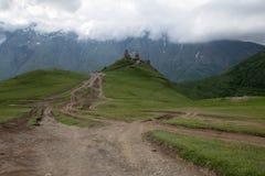 Kyrktaga i Kaukasus berg i Kazbegi, Georgia Arkivbild