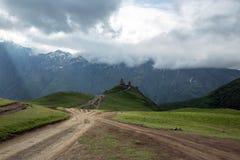 Kyrktaga i Kaukasus berg i Kazbegi, Georgia Arkivfoton