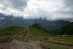 Kyrktaga i Kaukasus berg i Kazbegi, Georgia Fotografering för Bildbyråer