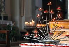 Kyrktaga med kandelaber och tända stearinljus under bönerna av Royaltyfri Fotografi