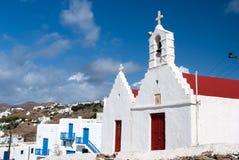Kyrktaga med klockatornet i Mykonos, Grekland Arkitektur för kyrklig byggnad på blå himmel Hus på berglandskap royaltyfri bild