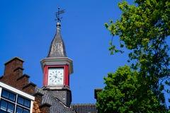Kyrktorn med en röd klocka Fotografering för Bildbyråer