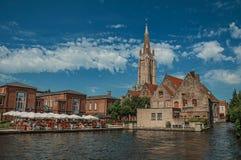 Kyrktorn och byggnader på kanal`en s kantar på Bruges Royaltyfri Bild