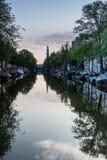 Kyrktorn reflekterad i Amsterdam kanaler arkivbilder
