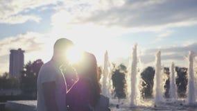 Kyss av ett älska par på en springbrunn- och solnedgångbakgrund HD 1920x1080 långsam rörelse arkivfilmer