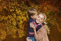 Kyss för lycklig son för stående stark hans moder i en parkera i hösten Arkivfoton
