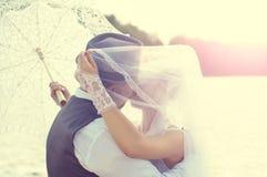 Kyssa bruden och brudgummen på solnedgången Arkivbilder