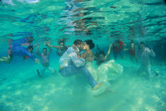 Kyssa för brud som och för brudgum är undervattens- med många par i bakgrunden Royaltyfri Fotografi