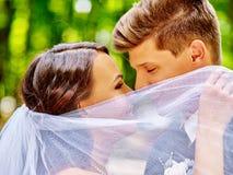 kyssa för brudbrudgum som är utomhus- Arkivbild
