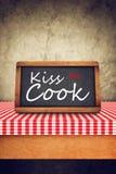 Kyssa kocken som Title på restaurang kritiserar den svart tavlan Arkivfoto