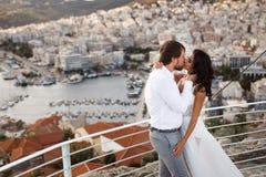 Kyssa med sikten för affektionpar överst av den Grekland staden, sommartid Precis gift lopp kopiera avst?nd royaltyfri bild