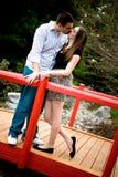 Kyssa på en röd bro Royaltyfri Fotografi