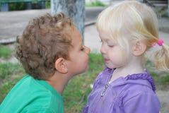 Kyssa så mig! Lilla flickan önskar att kyssa en pojke. Arkivfoto