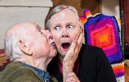 Kyssande äldre kvinna för äldre gentleman på kind Arkivfoto
