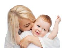 Kyssande behandla som ett barn le för lycklig moder Royaltyfri Bild