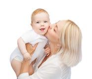 Kyssande behandla som ett barn le för lycklig moder Arkivbild