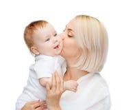 Kyssande behandla som ett barn le för lycklig moder Royaltyfri Foto