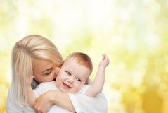 Kyssande behandla som ett barn le för lycklig moder Arkivbilder