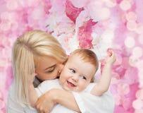 Kyssande behandla som ett barn le för lycklig moder Royaltyfria Bilder