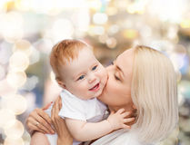 Kyssande behandla som ett barn le för lycklig moder Fotografering för Bildbyråer