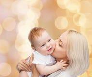 Kyssande behandla som ett barn le för lycklig moder Royaltyfria Foton